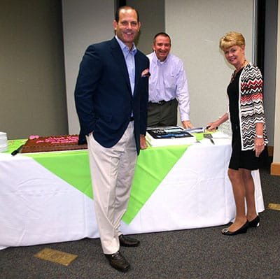 Kindred Chief Operating Officer Ben Breier and RehabCare President Pat Henry prepare to cut the cakes at the Smart luncheon.