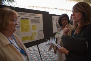 Attendees talk to Brenda Mayfield and Tanya Trotter about their poster presentation.