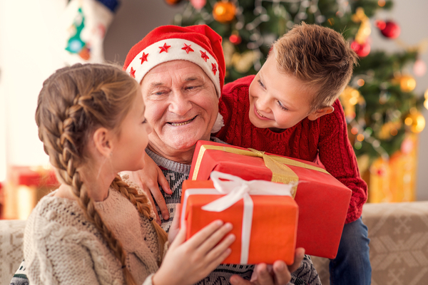 Image of two children giving grandfather a holiday gift