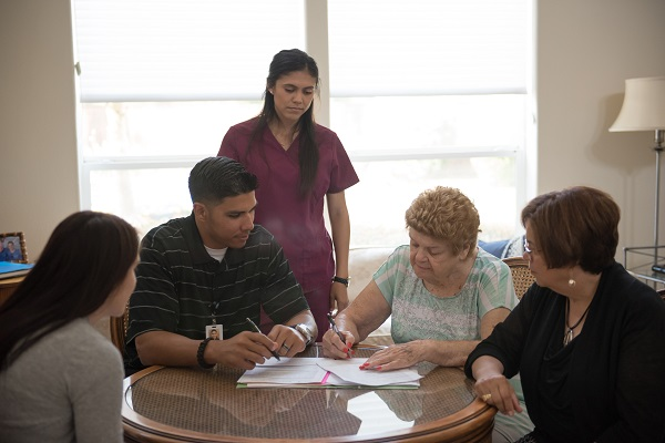 Image of a woman signing her advance directive document at the kitchen table surrounded by family
