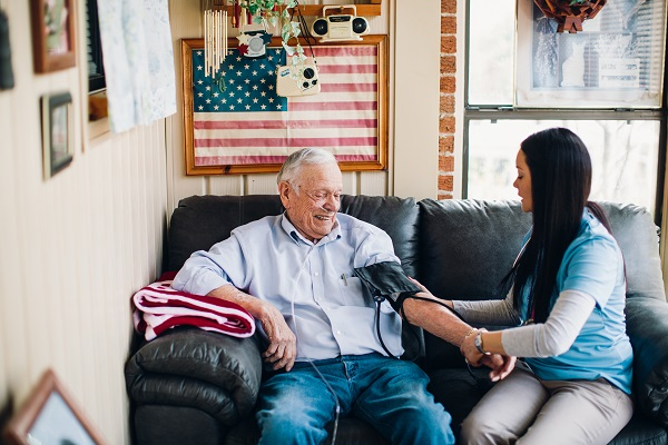Image of older man having his blood pressure checked at home by a home health nurse
