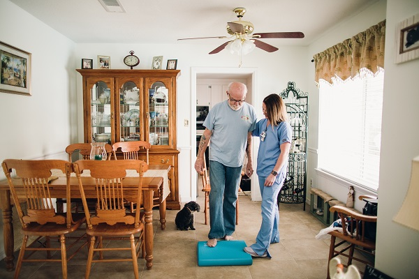 Image of a man in an in-home physical therapy session with his therapist
