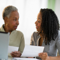 An adult daughter explaining Medicare coverage to her senior mother