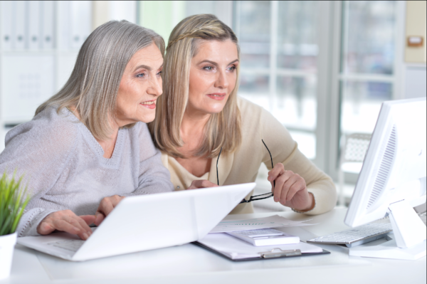 Image of older mother and adult daughter reviewing Medicare online