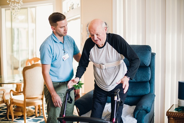 Image of a physical therapist helping an older man out of a recliner chair at home