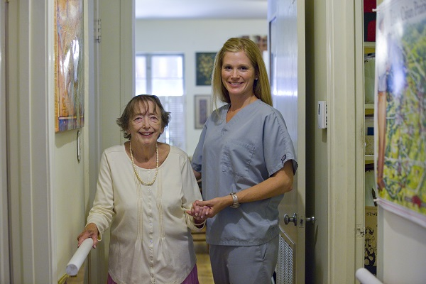 Image of a hospice nurse with a senior female patient in her home