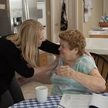 Image of a personal home care assistance speaking with a senior woman at the kitchen table