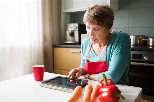 Image of a woman at her kitchen table researching on a tablet