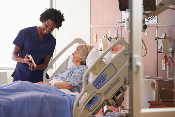 Image of a senior female patient in a hospital bed speaking with her nurse about her plan of care